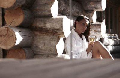 Frau sitzt vor Außensauna im Kunzmann's