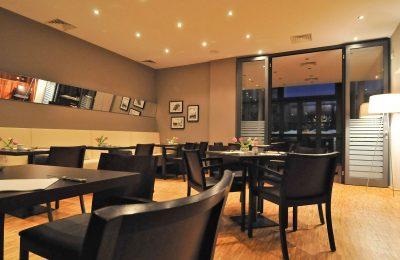 Helles Restaurant mit schwarzen Tischen und Stühlen