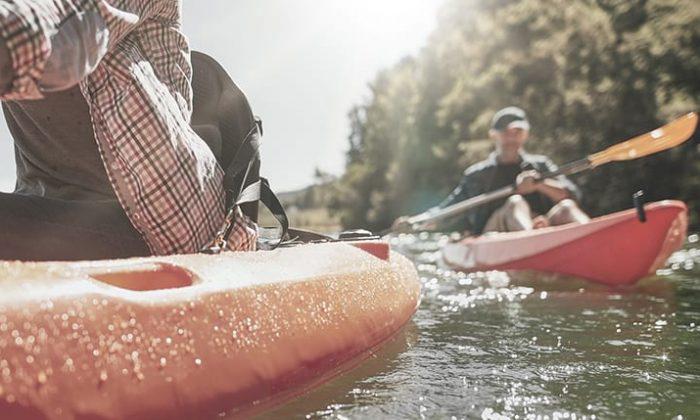 Zwei Menschen paddeln auf Booten
