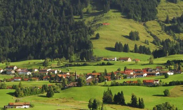 Landschaftsaufnahme vom Allgäu mit grünen Wiesen, Wäldern und einem Dorf