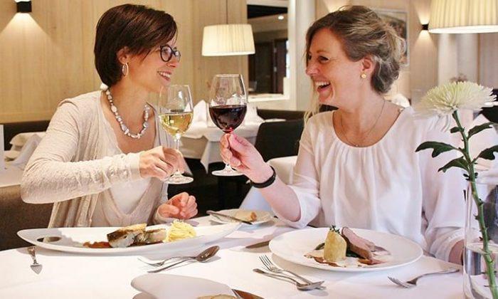 Zwei Frauen speisen und  trinken Wein