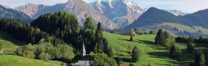 Landschaft des Allgäus mit grünen Wiesen, Holzhütten und Bergen