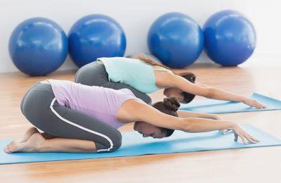 Zwei Frauen dehnen sich beim Yoga
