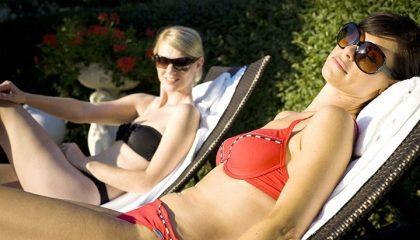 Zwei Frauen im Bikini entspannen am Pool