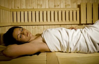 Frau in weißem Handtuch genießt Saunagang