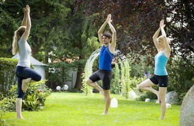 Menschen machen Yoga im Garten