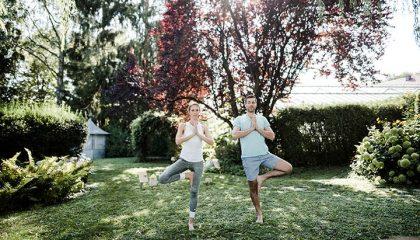 Paar macht gemeinsam Yoga im Garten