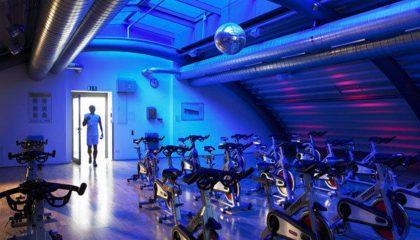 Blau beleuchteter Raum mit Trainingsgeräten im Fitnessclub