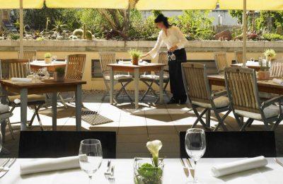Frau deckt Tisch im Garten