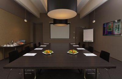 Schwarzer Tisch mit Stühlen und Leinwand für Tagungen