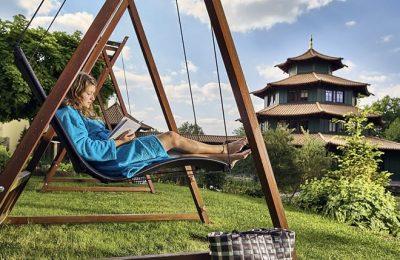 Frau entspannt im Garten in Schaukellieg
