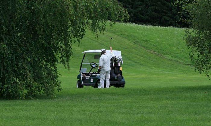 Mann neben Golfwagen