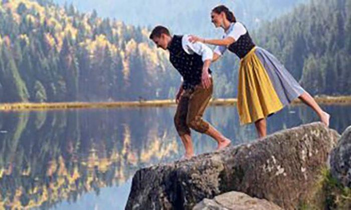 Paar in Dirndel und Trachten an einem See