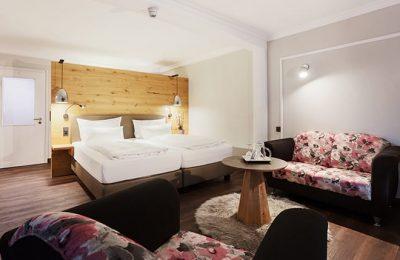 Bett und Wohnraum in den neuen Doppelzimmern