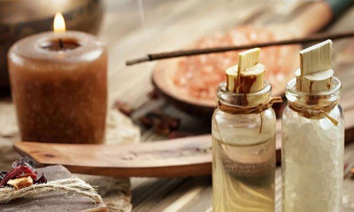Braune Kerze, Duftstäbchen und kleine Glasflaschen mit Ölen