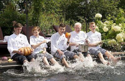 Küchenteam sitz gemeinsam am Pool mit Füßen im Wasser