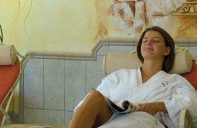 Frau in weißem Bademantel entspannt in der Ruhezone