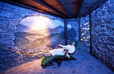Frau in weißem Bademantel liegt auf Liege im blau beleuchteten Salzstollen