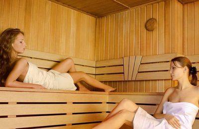 Zwei Frauen in weißen Handtüchern erholen sich in der Sauna