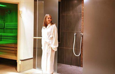 Frau in weißem Bademantel vor Dampfbad