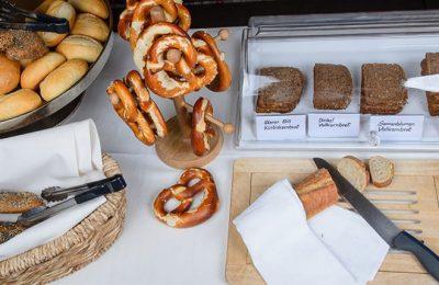 Frühstücksbuffet mit verschiedenen Brotsorten und Brezeln
