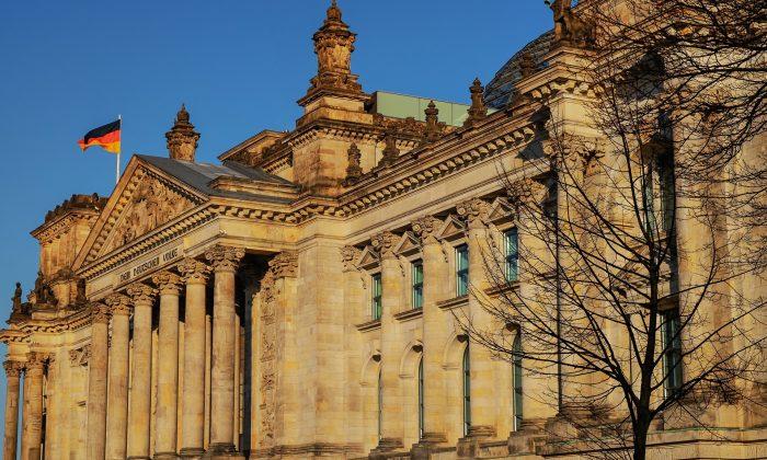 Der Reichstag in Berlin von der Seite vor blauem Himmel