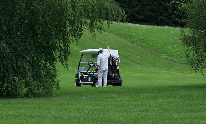 Golfspieler neben Golfcaddy.