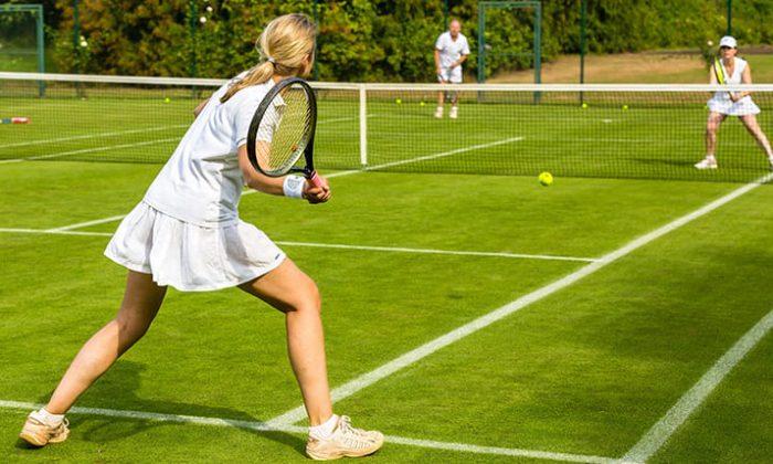 Menschen spielen Tennis auf einem Rasenplatz