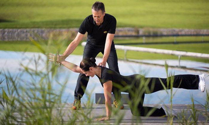 Frau wird unterstützt bei Yoga Übung durch Trainer