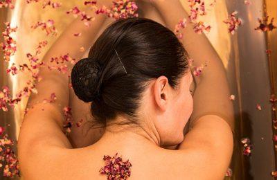 Frau genießt Massage mit Blüten