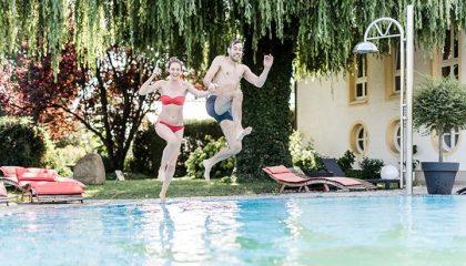 Junges Paar springt in den Außenpool