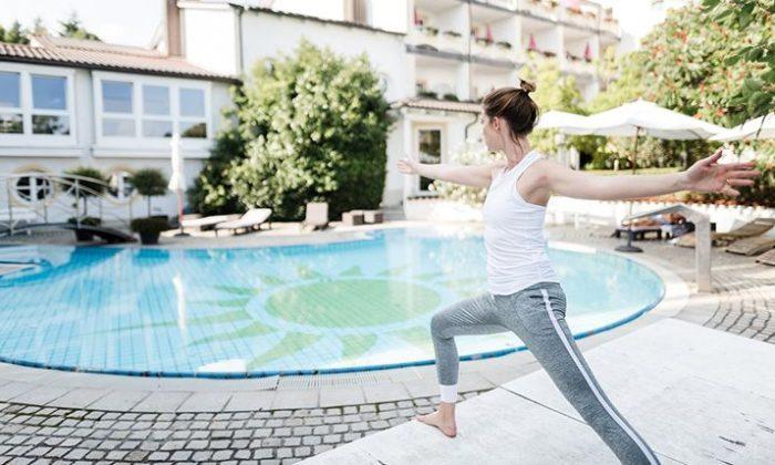 Frau macht Yoga vor dem Außenpool