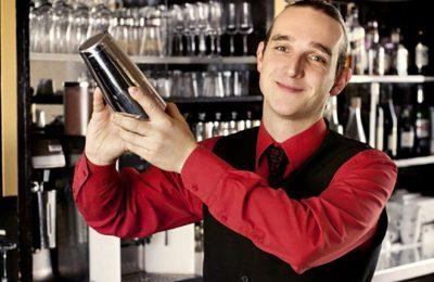 Barkepper im roten Hemd an der Bar