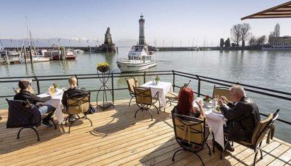 Menschen speisen auf der Hafenterrasse des Hotels