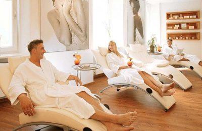 Mann und Frau in weißen Bademänteln entspannen auf Liegen