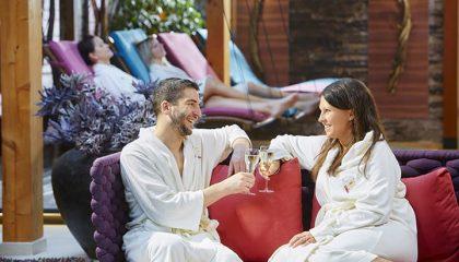Paar in weißen Bademänteln stößt mit Sekt an