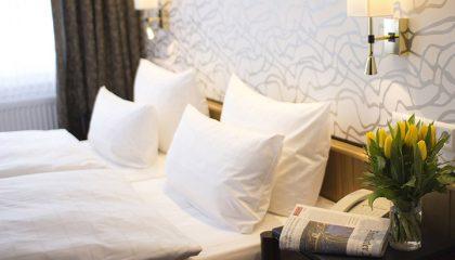 Bett mit vier weißen Kissen im  Doppelzimmer Classic