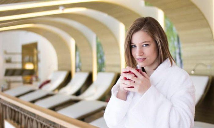 Frau in weißem Bademantel trinkt Tee im Spa