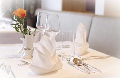 Fein gedeckter Tisch mit gefalteten Servietten
