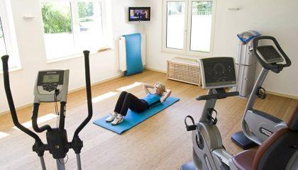 Frau macht Sport im Fitnessraum neben Trainingsgeräten