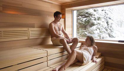 Paar entspannt in Sauna mit Ausblick im Winter