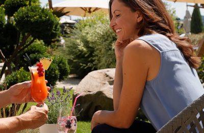 Frau wird Cocktail im Garten serviert