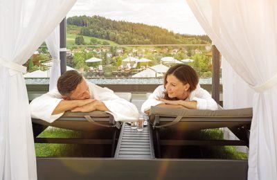 Paar in weißen Bademänteln entspannt im Garten