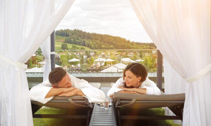 Paar entspannt auf Himmelbett im Garten