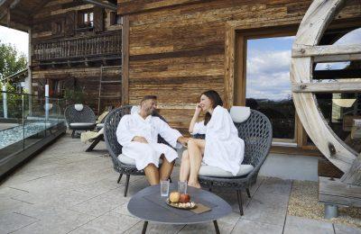 Paar in weißen Bademänteln macht es sich nach Saunagang gemütlich