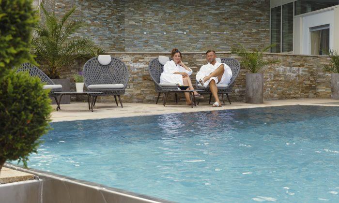 Paar in weißen Bademänteln relaxt neben dem Außenpool