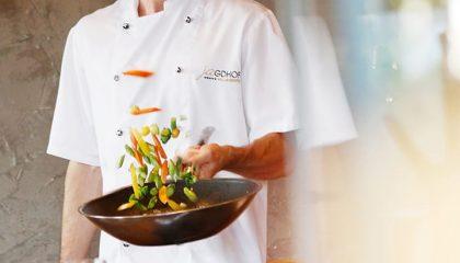 Koch vom Hotel Jagdhof wendet Essen in einer Pfanne