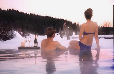 Mann und Frau genießen Sonnenuntergang vom Pool aus
