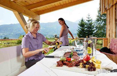 Zwei Frauen speisen an der Holzhütte