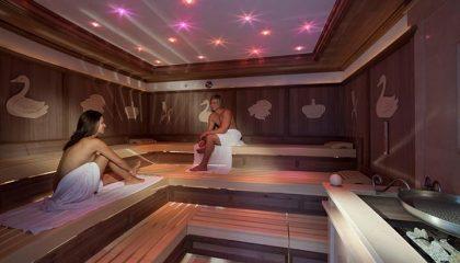 Paar schwitz in Sauna mit rosa Licht